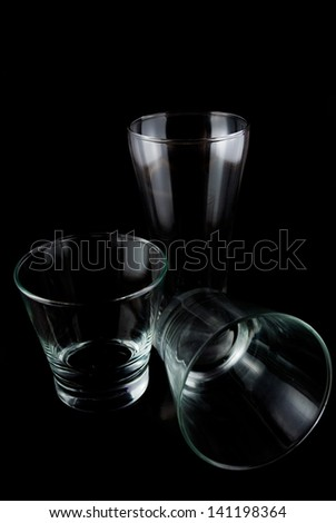 Empty glasses for whiskey on a reflective surface on black background - Empty glasses on a black background