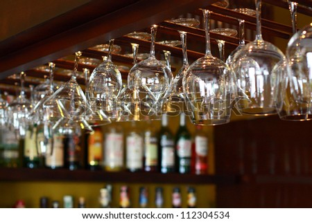 Empty glasses for wine above a bar rack - stock photo