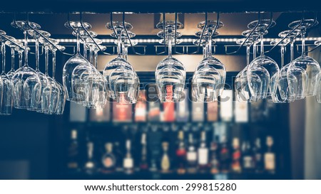 Empty glasses for wine above a bar rack in vintage tone. - stock photo