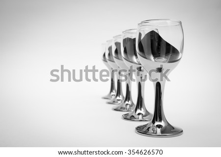 Empty glasses in restaurant, black and white photo.glasses on black and white background - stock photo