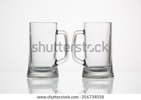 Empty glasses of beer on the glass desk - stock photo