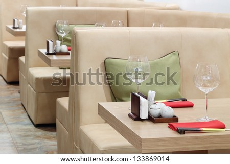 Empty glasses on tables and beige leather sofas in Japanese restaurant.