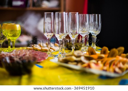 empty glasses stand on a festive table with food preparation for the wedding feast - stock photo