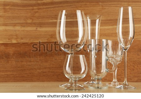 Empty goblets on wooden background - stock photo
