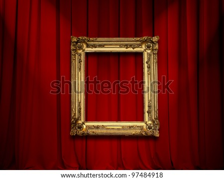 Empty golden painting frame on red curtain wall - stock photo