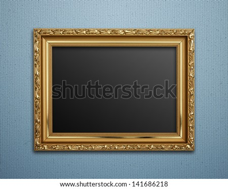 Empty golden vintage frame on wallpaper background - stock photo