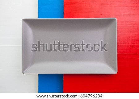 Empty gray ceramic dish on over white,blue and red wooden table, rectangle dish