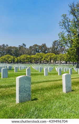Empty green grass field full of white grave headstones. - stock photo