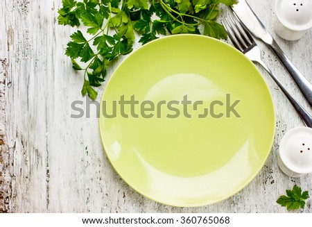 Empty green plate and fresh parsley on rustic white wooden background, place for text - stock photo