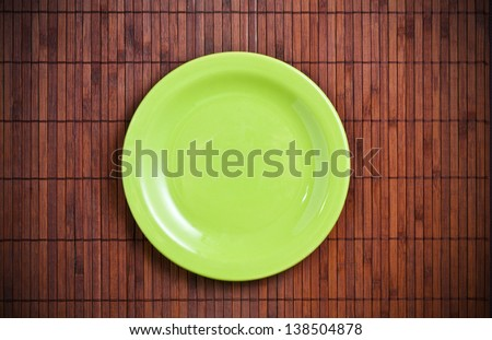 Empty green plate on wooden table - stock photo