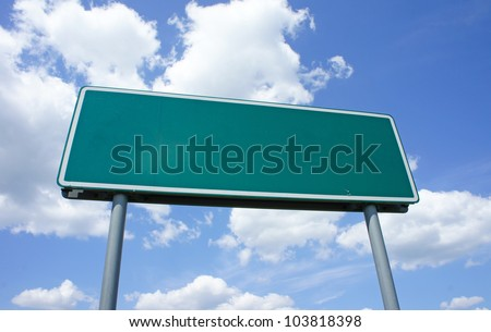 Empty green road sign against blue sky with clouds - a place for your own text on a green sign. - stock photo