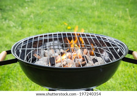 Empty grill on garden with burning embers - stock photo
