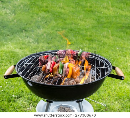 Empty grill with fire flames placed on garden lawn - stock photo