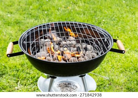 Empty grill with fire on garden - stock photo