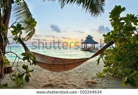 Empty hammock in the tropical beach in the Maldives at sunset - stock photo