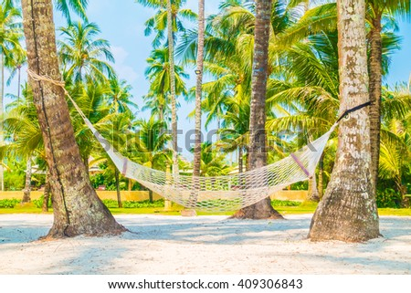Empty hammock on beautiful tropical beach and sea with coconut palm tree - Boost up color Processing