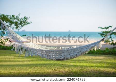 Empty hammock under palm trees at tropical beach with ocean on back - stock photo