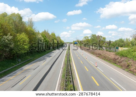 Empty highway in front of blue sky - stock photo