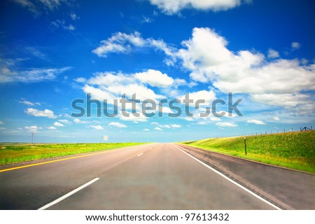 Empty highway in Midwest with green grass and blue sky in summer en route to Chicago - stock photo