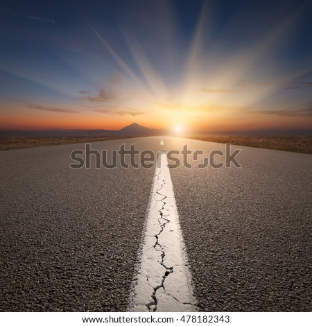 Empty highway leading to the mountains through the desert against the rising sun with big sunbeams at beautiful sunrise. Success concept.