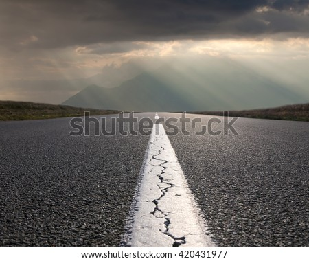 Empty highway leading to the mountains through the desert against the sun rays at beautiful morning.
