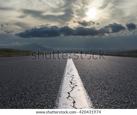 Empty highway leading to the mountains through the plain against the rising sun at beautiful morning. - stock photo