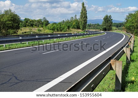 Empty highway passing landscape trees, mountains in the background, view from eye level - stock photo