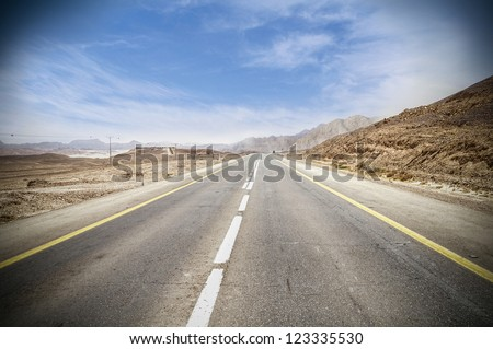empty highway surrounded by hills in Arava desert - stock photo
