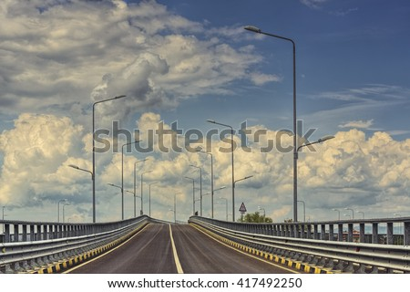 Empty highway with lampposts over dramatic cumulus clouds in the sky. - stock photo