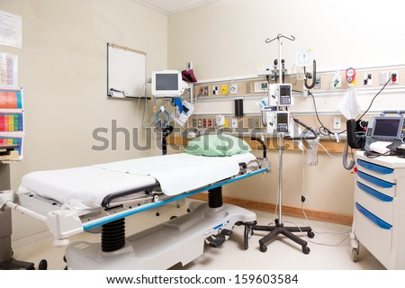 Empty hospital bed with emergency equipment