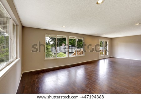 Empty house in light ivory color with hardwood floor and large window
