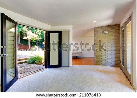 Empty house interior. Room with brick wall trim and carpet floor. View of open door to backyard - stock photo
