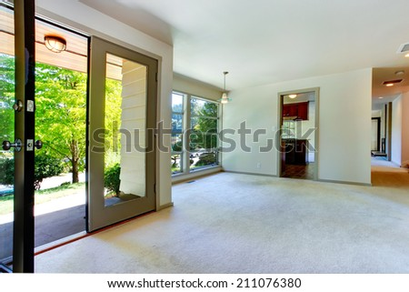 Empty house interior. Room with carpet floor and glass wall. View of glass door to backyard