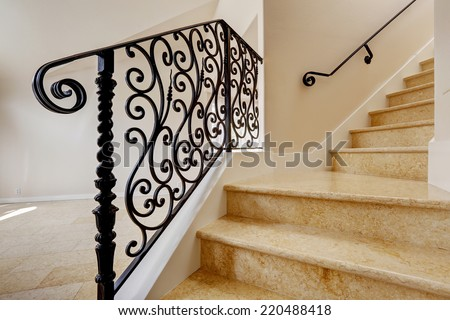 Empty house interior with shiny tile floor. Marble staircase with black wrought iron railing - stock photo