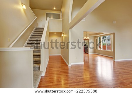 Empty house with hardwood floor, high ceiling and light ivory walls