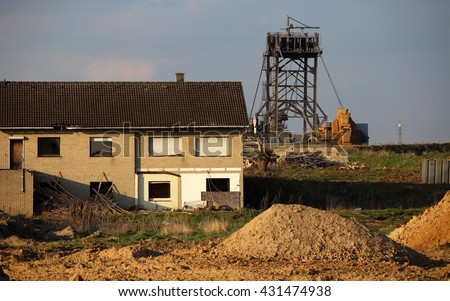 Empty houses of the  city of Erberich awaiting destructing due to further mining of coal. A large bucket wheel excavator digging lignite in the background, Nordrhein Westfalen, Germany - stock photo