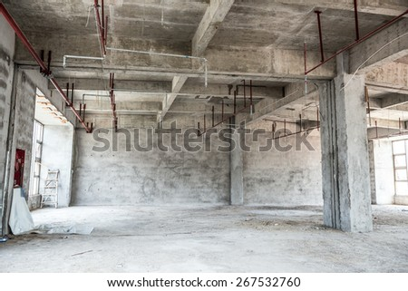 Empty industrial loft in an architectural background with bare cement walls, floors and pillars supporting a mezzanine - stock photo