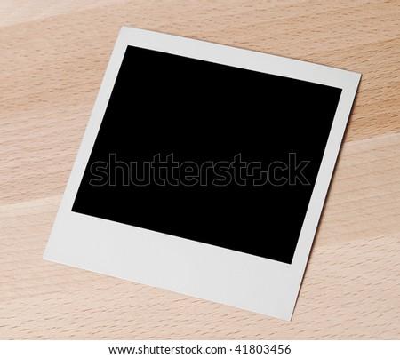 Empty instant camera frame on wooden desk. - stock photo