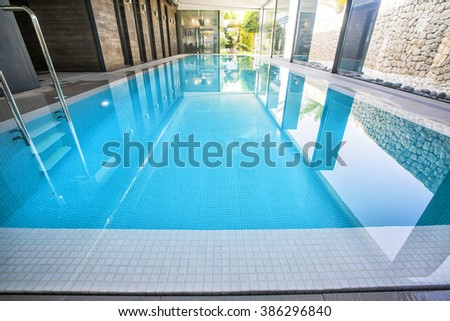 Empty interior swimming pool with relaxation area in a modern hotel. - stock photo