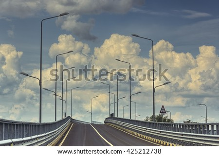 Empty interstate road with highway lamp posts over cumulus clouds in the sky. - stock photo