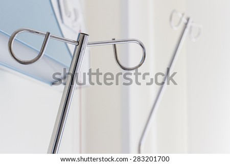 Empty intravenous pole hanger for serum, blood and pharmaceutical bags in brightly lit hospital room at treatment end. Natural sunlight gives a positive feeling of patient's successful full recovery. - stock photo