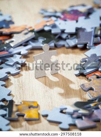 Empty jigsaw puzzle surrounded by pieces  on a table . Shallow depth of field - stock photo
