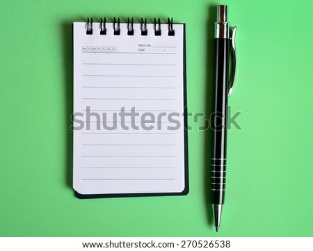 Empty jotter with pen on background - stock photo