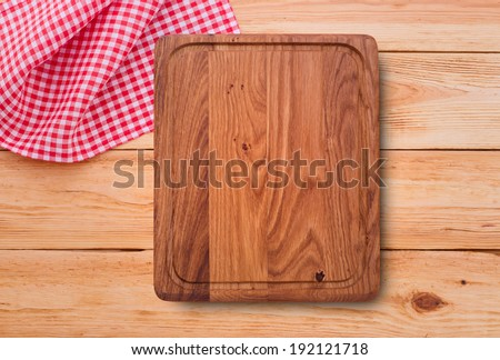 Empty kitchen cutting board. Wooden table covered with red checked tablecloth. View from top.  - stock photo