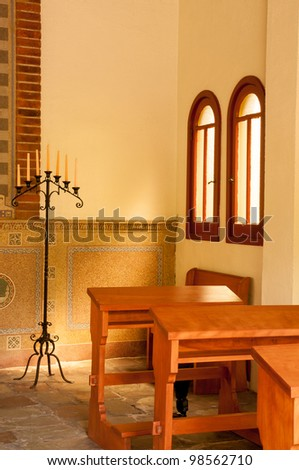 Empty kneelers in a church with light shining through the window on candles - stock photo