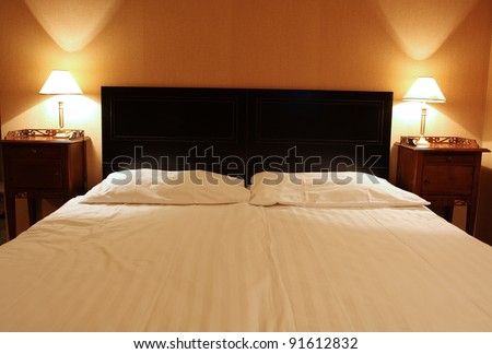 empty large bed for two with the lamps at the heads - stock photo