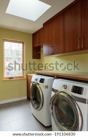 Empty laundry room with skylight/Vertical shot of washer and dryer inside a model home laundry room - stock photo