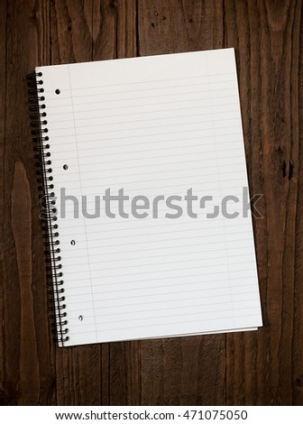 Empty lined ringbinder page with copy space for your message on a dark wooden desktop background