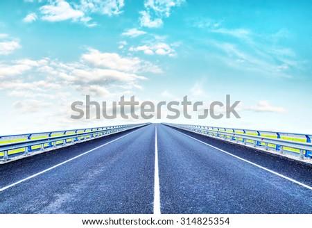 Empty lonely highway goes ahead to horizon - stock photo