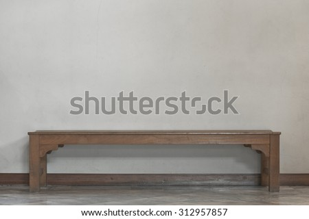 Empty long wooden chair in front of plain yellow rough surface concrete wall